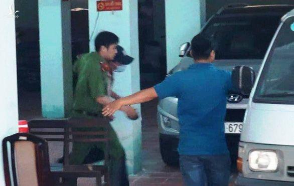 Cơ quan chức năng đưa Nguyễn Hải Nam (bịt mặt) lên xe biển xanh rời TAND quận 4 - Ảnh: NGỌC KHẢI