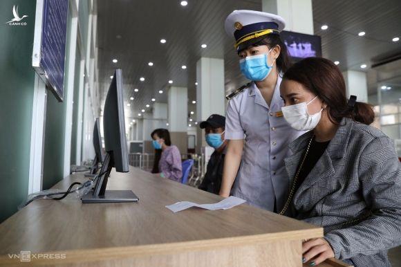 Nhân viên cửa khẩu quốc tế Mộc Bài hướng dẫn người dân kê khai y tế khi nhập cảnh ngày 22/3. Ảnh: Hữu Khoa.