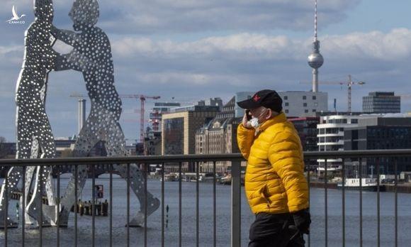 Người đàn ông đeo khẩu trang phòng dịch trên đường phố Berlin, Đức hôm 21/3. Ảnh: AFP.