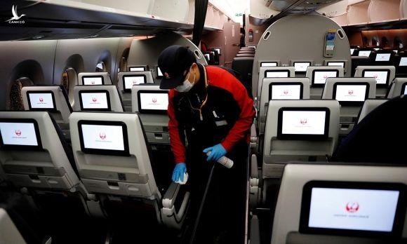 Nhân viên một hãng hàng không Nhật Bản dọn dẹp khoang máy bay tại sân bay Haneda, Tokyo, hôm 26/5. Ảnh: Reuters.