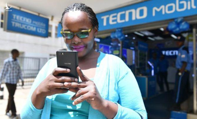 Một phụ nữ đứng bên ngoài cửa hàng Tecno ở châu Phi. Ảnh: Govandbusinessjournal.