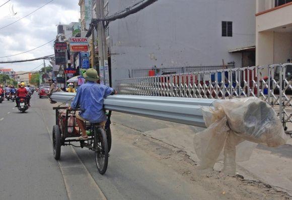 Người đàn ông chạy xe ga gác chở tôn cồng kềnh trên đường Phan Văn Trị, quận Gò Vấp, năm 2020. Ảnh: Gia Minh.
