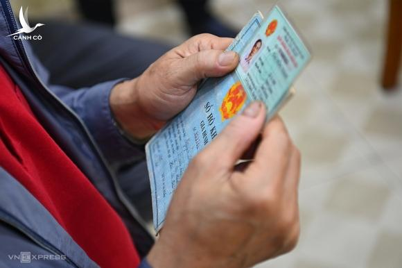 Một người dân cầm chứng minh thư và hộ khẩu giấy đi làm thẻ căn cước công dân gắn chip, ngày 9/3. Ảnh:Giang Huy