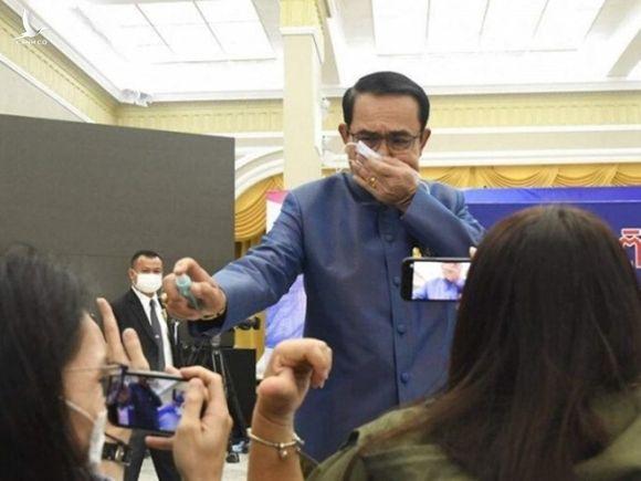 Thủ tướng Prayut Chan-o-cha phun nước rửa tay vào mặt phóng viên trong cuộc họp báo ngày 9-3. Ảnh: HAYAT