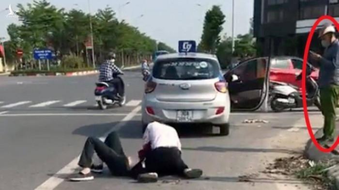 Hình ảnh Đại úy công an xã Cự Khê, huyện Thanh Oai thờ ơ, đứng gọi điện thoại tại hiện trường vụ cướp taxi