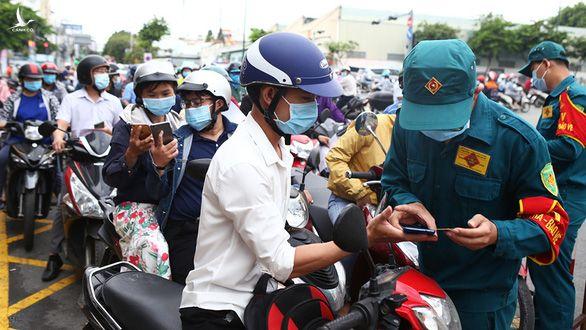 Lực lượng chức năng hướng dẫn người dân khai báo y tế tại chốt trạm Phan Văn Trị (TP.HCM) trong những ngày giãn cách.