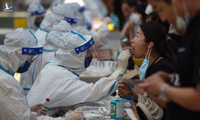 Nhân viên y tế lấy mẫu xét nghiệm nCoV cho người dân tại thành phố Nam Kinh, tỉnh Giang Tô, Trung Quốc, hôm 21/7. Ảnh: AFP.