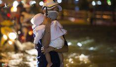 Triều cường đạt đỉnh, người TP Hồ Chí Minh bỏ xe bế con qua đường ngập