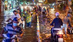 Người dân TP.HCM bì bõm lội nước về nhà trong mưa lớn